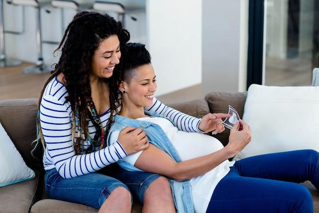 Pareja de lesbianas embarazadas sentada en el sofá y mirando el informe de ecografía