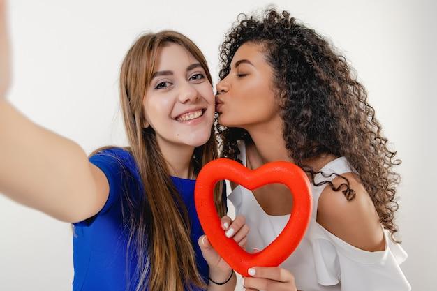 Pareja de lesbianas haciendo selfie con figura en forma de corazón rojo aislado