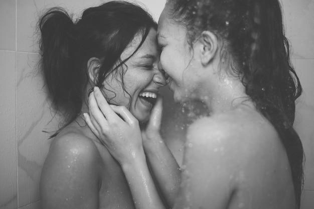 Pareja de lesbianas homosexuales en la ducha, riendo