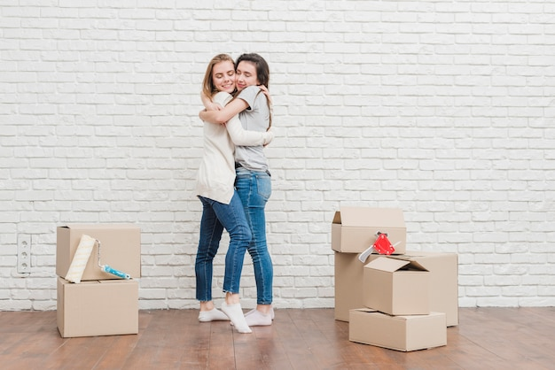 Pareja de lesbianas jóvenes abrazándose en su nueva casa contra la pared de ladrillo blanco
