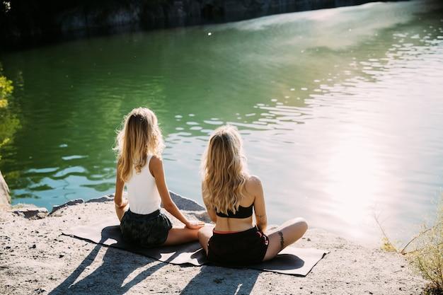 Pareja de lesbianas jóvenes divirtiéndose en riverside en día soleado