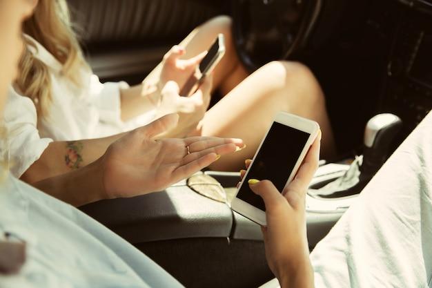 Pareja de lesbianas jóvenes preparándose para viaje de vacaciones en el coche en un día soleado