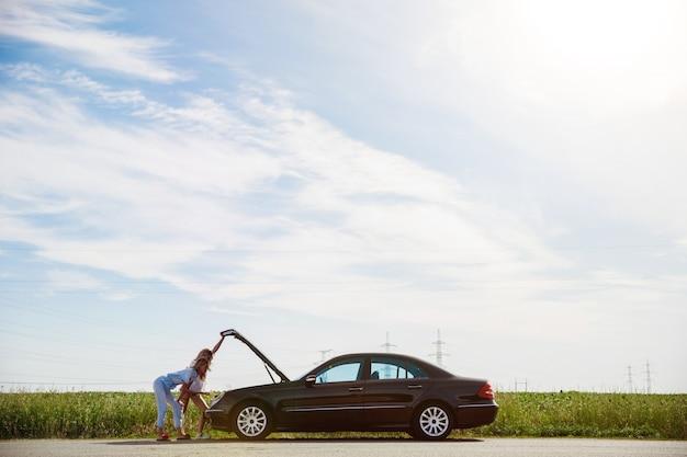 Pareja de lesbianas jóvenes que van de viaje de vacaciones en el coche en un día soleado