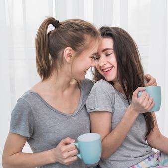 Pareja de lesbianas jóvenes románticas felices en camiseta gris sosteniendo una taza de café azul en la mano