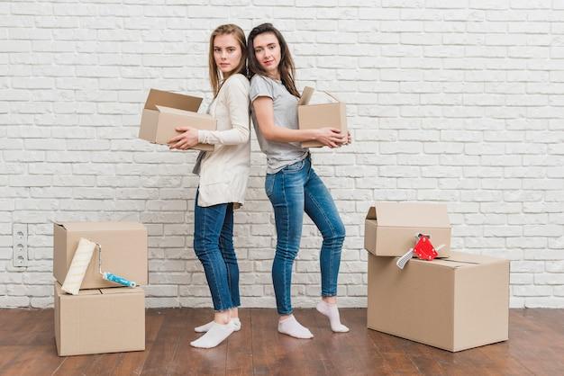 Pareja de lesbianas jóvenes sosteniendo cajas de cartón en movimiento en la mano de pie de espaldas contra la pared blanca
