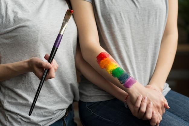 Pareja de lesbianas jóvenes tomados de la mano con la bandera pintada del arco iris en la mano
