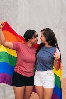 Pareja de lesbianas latinas con bandera lgtb en la ciudad. concepto lgbt