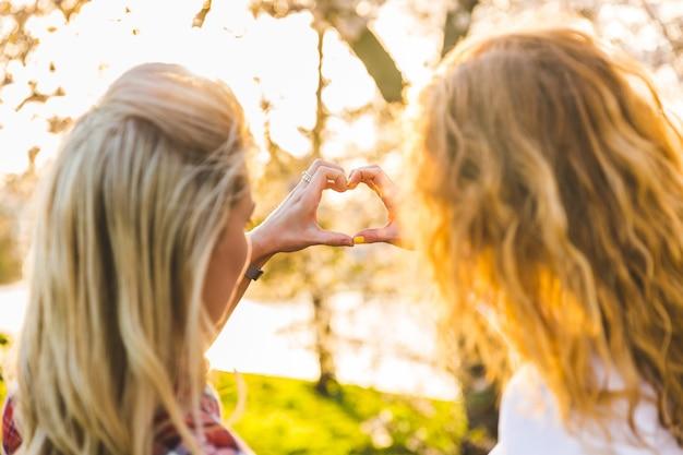 Pareja de lesbianas, manos en forma de corazón en el parque