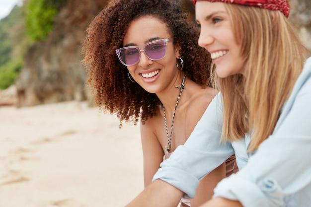 Pareja de lesbianas o amigas jóvenes cercanas tienen vacaciones en la playa tropical, miran la luz del sol con expresión complacida, tienen una verdadera historia de amor.