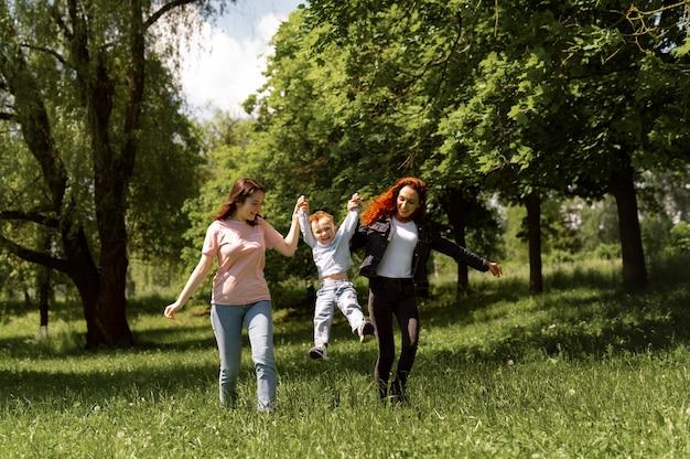 Pareja de lesbianas pasar tiempo con su hijo en el parque