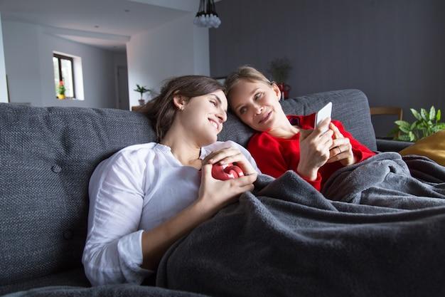 Pareja de lesbianas positiva descansando en el sofá