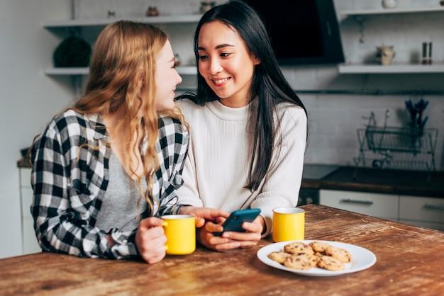 Pareja de lesbianas sentado en la mesa con teléfono inteligente
