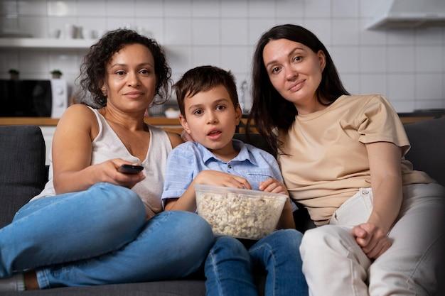 Pareja de lesbianas con su hijo viendo una película