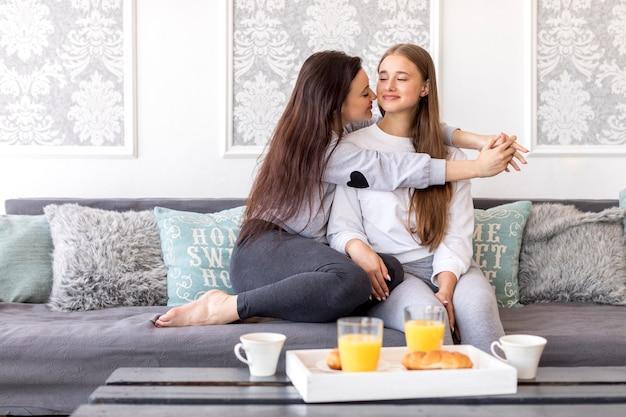 Pareja de lesbianas tiernas sentadas en un sofá con desayuno