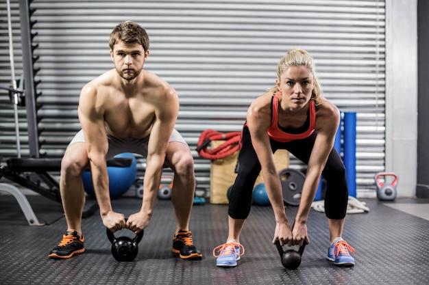Pareja levantando pesas juntos en el gimnasio de crossfit