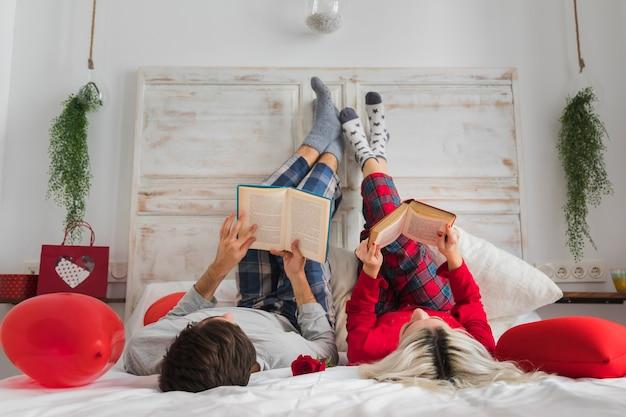 Pareja leyendo en la cama el día de san valentín