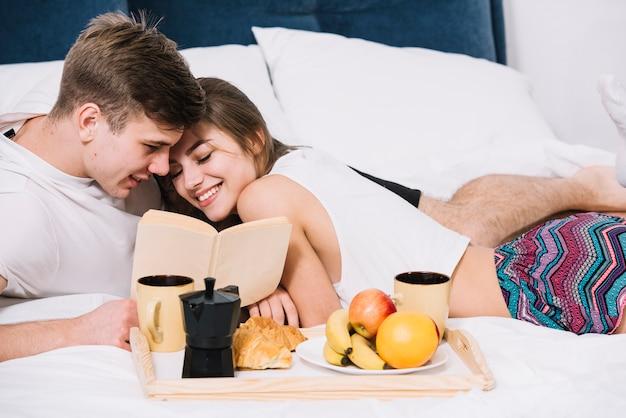 Pareja leyendo libro en cama con bandeja de comida
