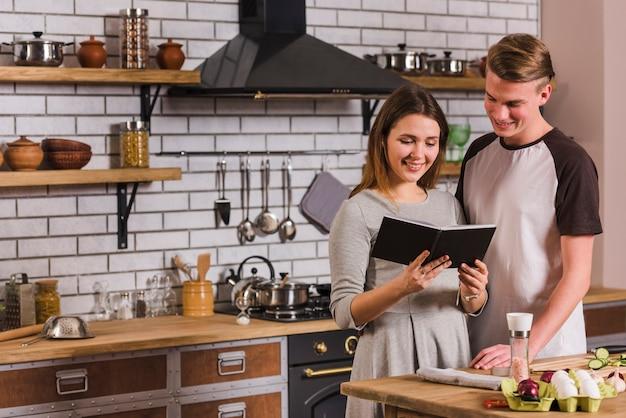 Pareja leyendo libro de recetas mientras cocinan juntos