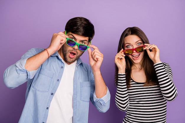 Pareja leyendo llenos de alegría usar gafas de sol y ropa casual aislado pared de color púrpura