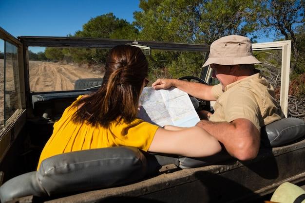 Pareja leyendo el mapa mientras está sentado en el vehículo