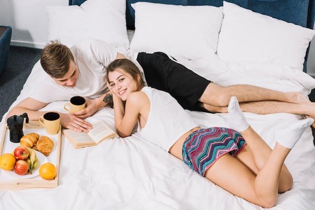 Pareja con libro de lectura de café en la cama