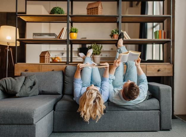 Pareja con libros tumbado en el sofá boca abajo