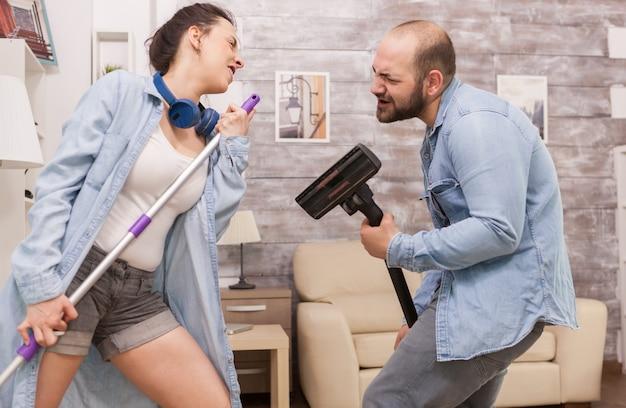 Pareja limpiando la casa y cantando en la aspiradora