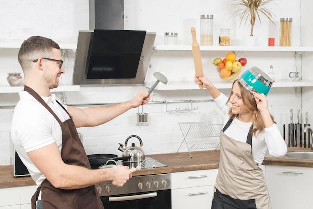 Pareja luchando de juego en la cocina