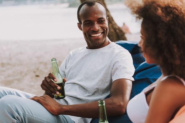 Pareja de luna de miel de raza mixta bebe cerveza en la playa