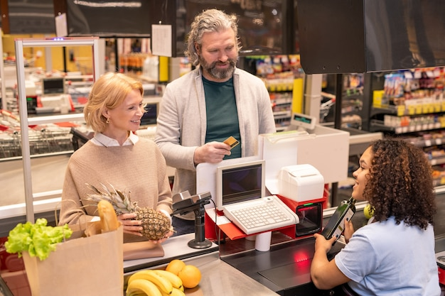 Pareja madura alegre de pie junto a la caja registradora delante del joven cajero de raza mixta escaneando lo que compraron en el supermercado