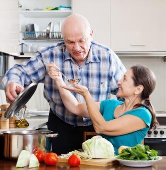 Pareja madura cocinando comida con verduras
