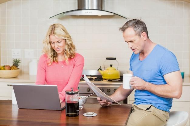 Pareja madura desayunando mientras usa una computadora portátil y leyendo en la cocina