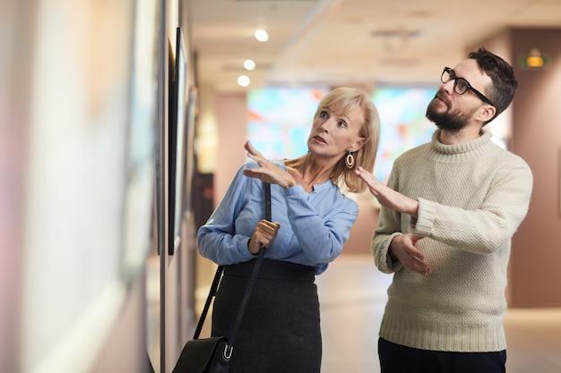 Pareja madura mirando pinturas en exposición de arte