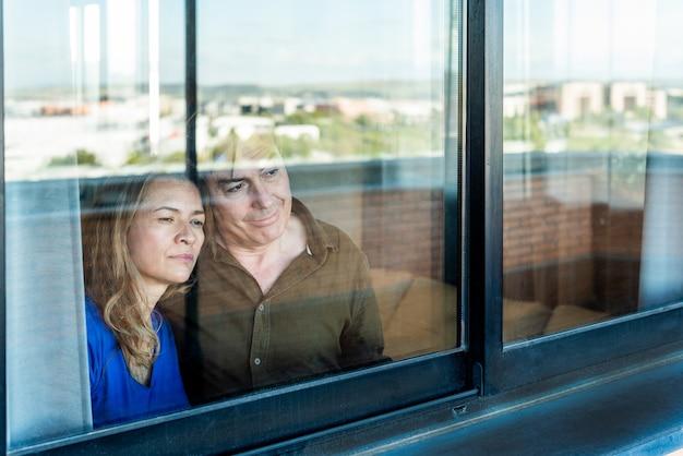 Pareja madura mirando triste por la ventana de casa. foto de alta calidad