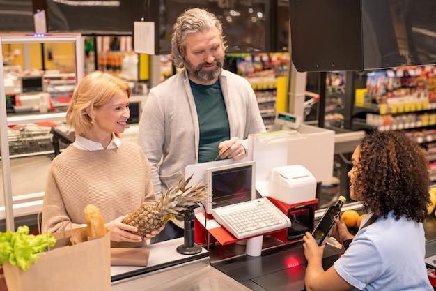 Pareja madura de pie junto al mostrador de caja en el supermercado mientras joven escaneando los productos alimenticios que compraron