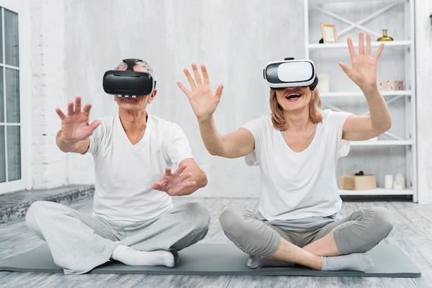 Pareja madura senior sentada en la alfombra gris divirtiéndose con gafas de realidad virtual