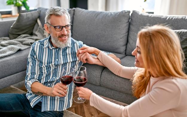 Pareja madura sentada en el suelo cerca del sofá con copas de vino, relajándose, disfrutando de la vida en casa.