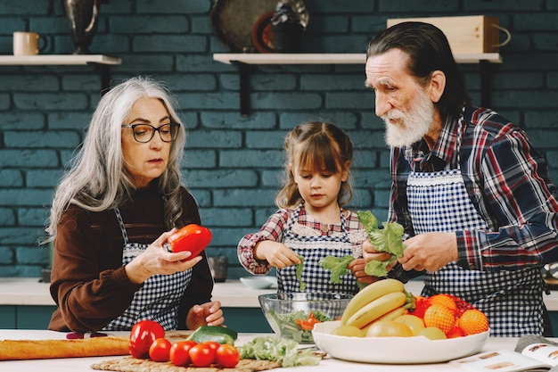 Pareja madura y su nieta preparando la comida
