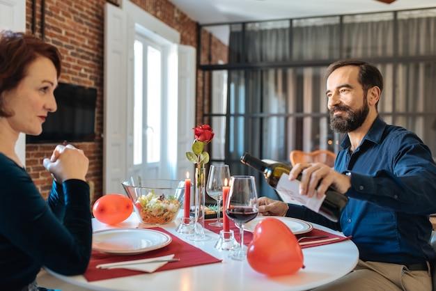 Pareja madura teniendo una cena romántica en casa para el día de san valentín y bebiendo vino tinto