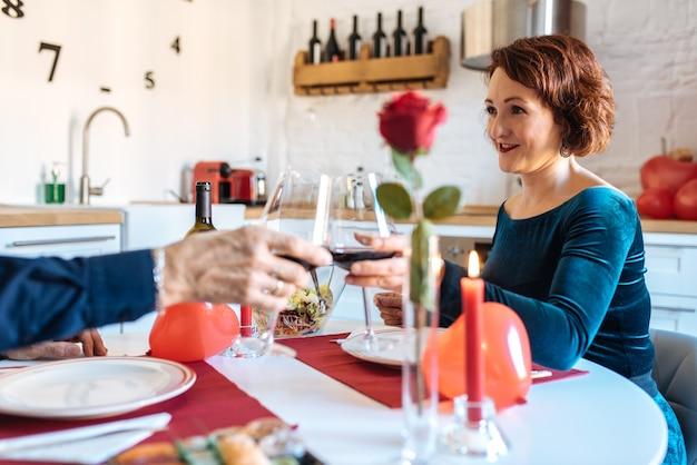 Pareja madura teniendo una cena romántica en casa para el día de san valentín y brindis con vino tinto
