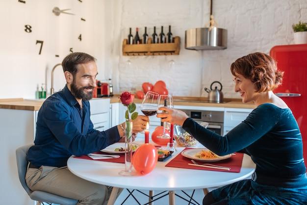 Pareja madura teniendo una cena romántica en casa para el día de san valentín