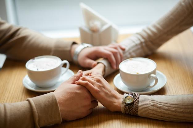 Pareja mantenga las manos tomando café en la cafetería