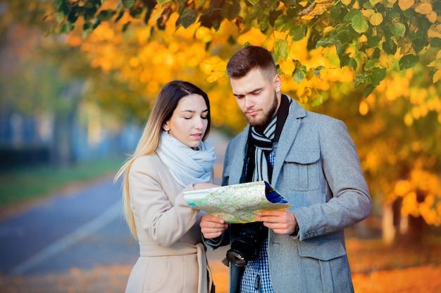 Pareja con mapa y cámara en callejón otoño de la ciudad.