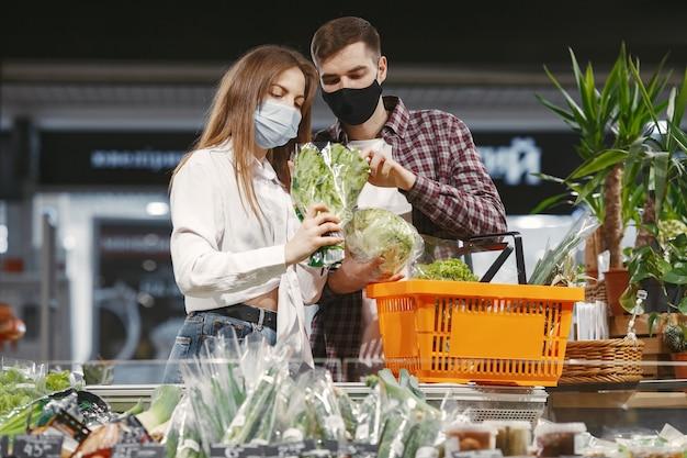 Pareja en máscara protectora médica en un supermercado.