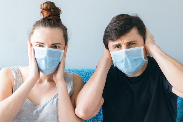 Pareja con mascarillas médicas sosteniendo sus cabezas con sus manos