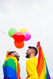 Pareja masculina alegre que cubre en la bandera del arco iris en el desfile del orgullo gay