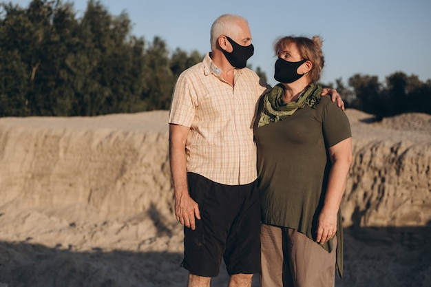Pareja mayor al aire libre con máscara médica para protegerse del coronavirus en un día de verano