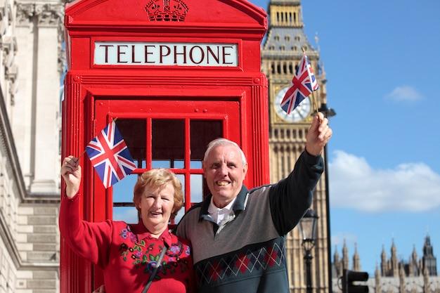 Pareja mayor alegre con banderas británicas