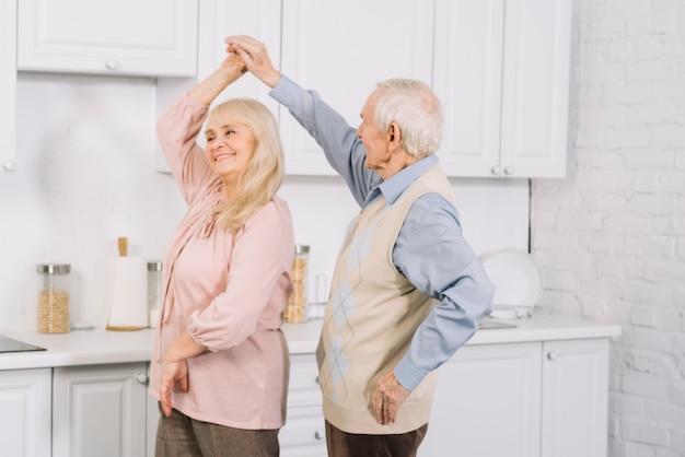 Pareja mayor bailando en cocina