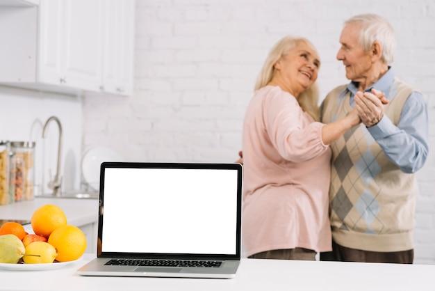 Pareja mayor bailando detrás de portátil en cocina